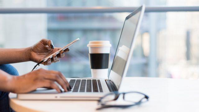 カフェでパソコンとスマホを扱う人