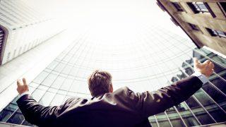 ビル群から空を見上げる男性