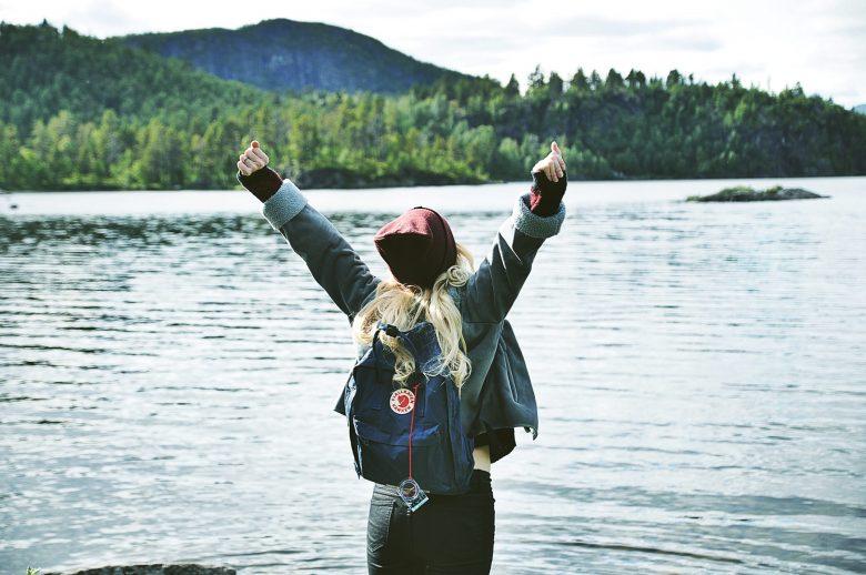 湖のまわりで体を伸ばす女性