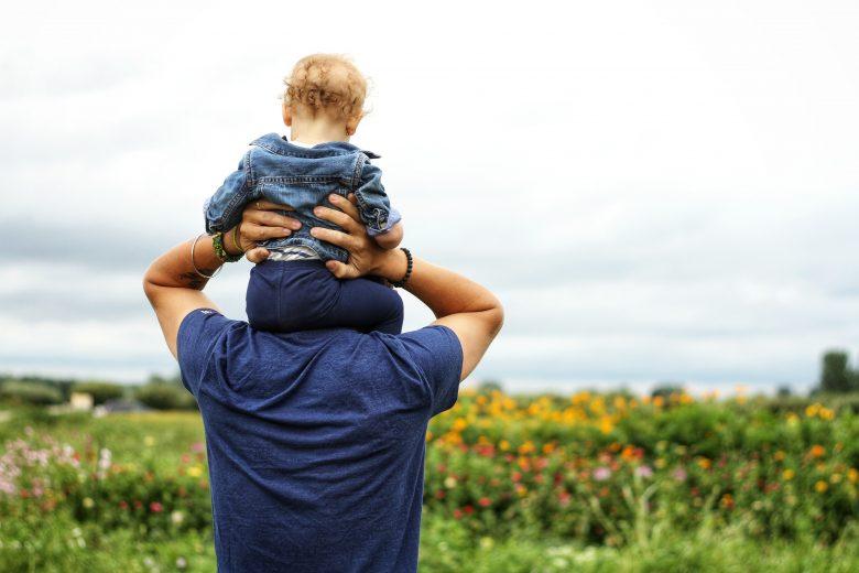 子供を抱えて草原を散歩する男性