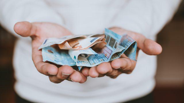 2ユーロ紙幣を手の上に広げる人