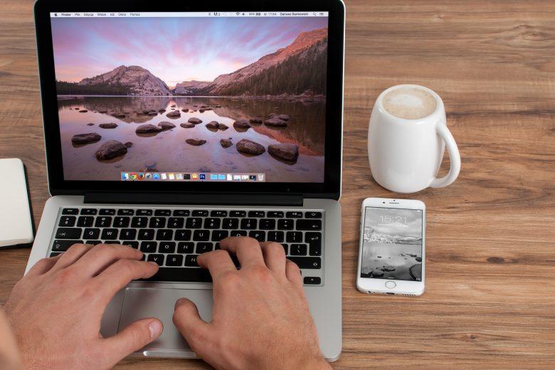 コーヒーを飲みながらパソコンを操作する人