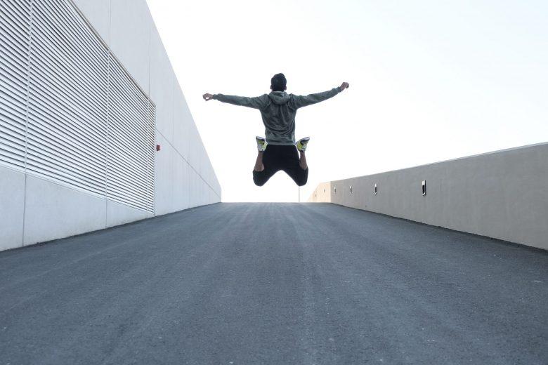 両手を広げてジャンプする灰色のパーカーを着た人