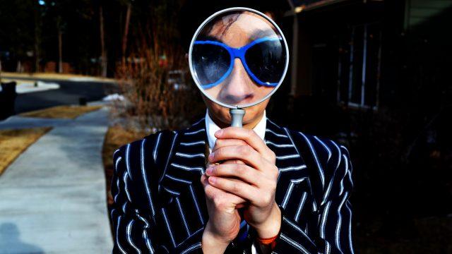 スーツを着て虫眼鏡を使用している人