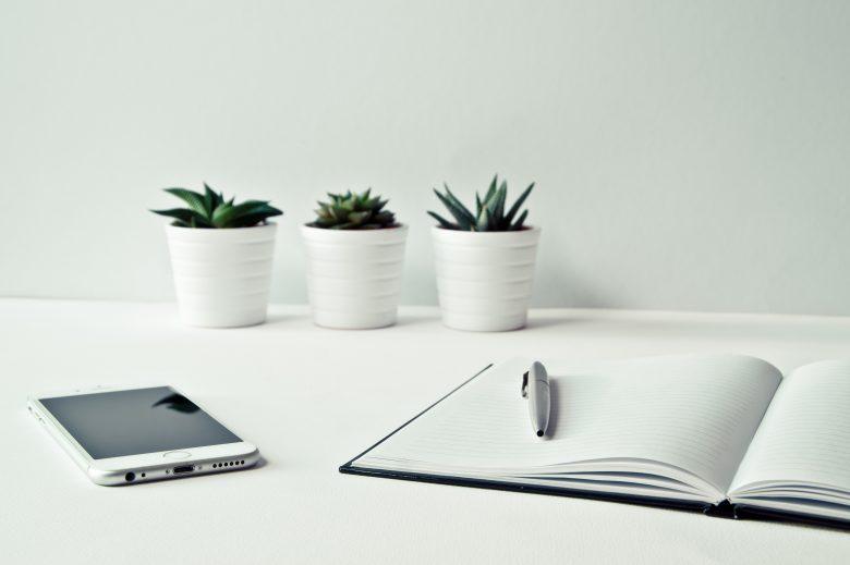 3つの白い植木鉢がスマホとノートの前に並ぶ