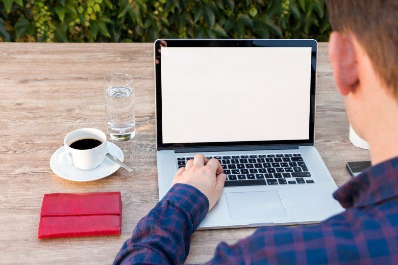 コーヒーを飲みながらパソコンを操作する男性