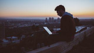 コンクリートの上に座ってパソコンを使う男性