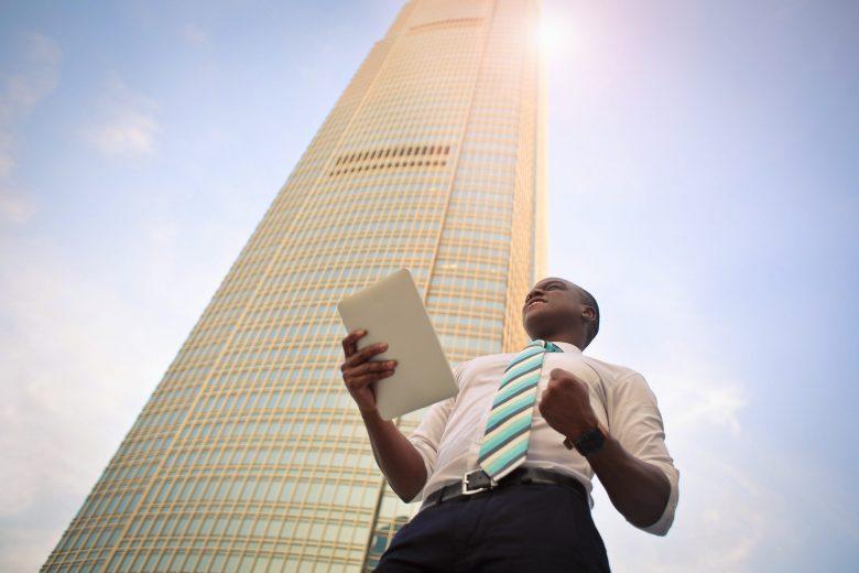 高層ビルの前に立ってガッツポーズをする男性
