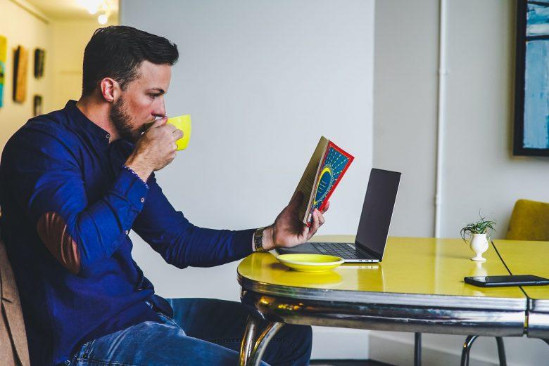 イスに座り本を読みながらコーヒーを飲む男性