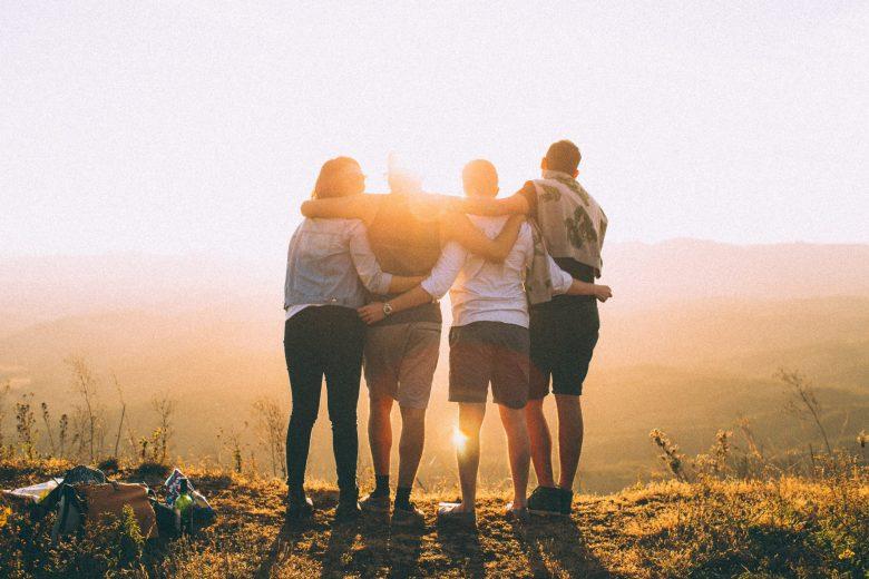太陽を見ながら肩を組む仲間たち
