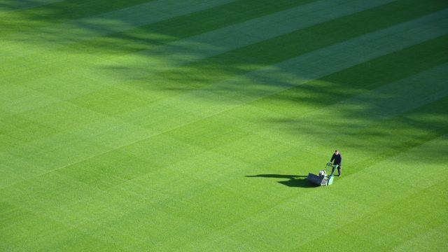 日中のスポーツフィールドをトリミングする人の航空写真