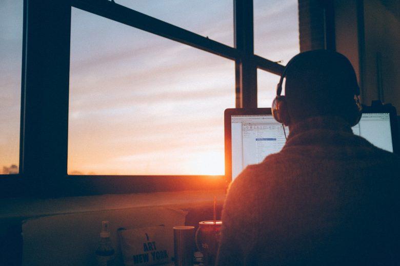 ヘッドフォンをしてパソコンを操作する人