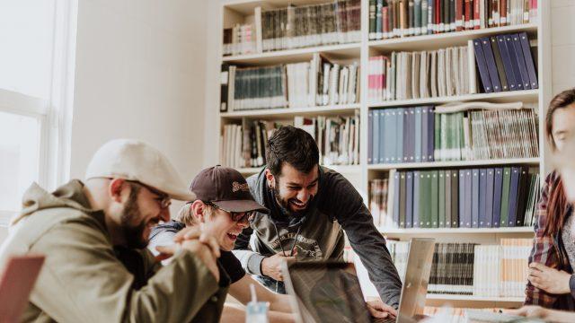 パソコン画面を見て笑い合う3人の男性たち