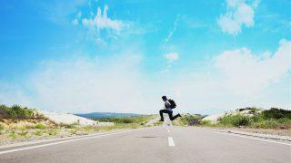天気の良い日の路上でジャンプする男性
