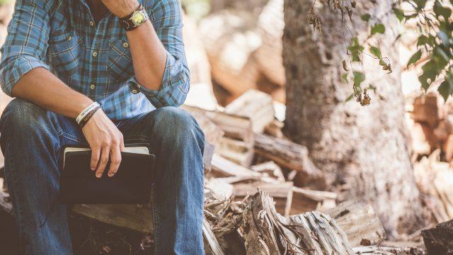 木材の上に座って考える男性