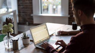 テーブルでノートパソコンを操作する男性