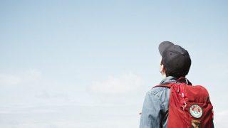 赤いリュックを背負って空を見上げる人