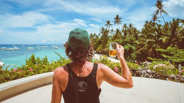 景色をみながらビールを飲む男性