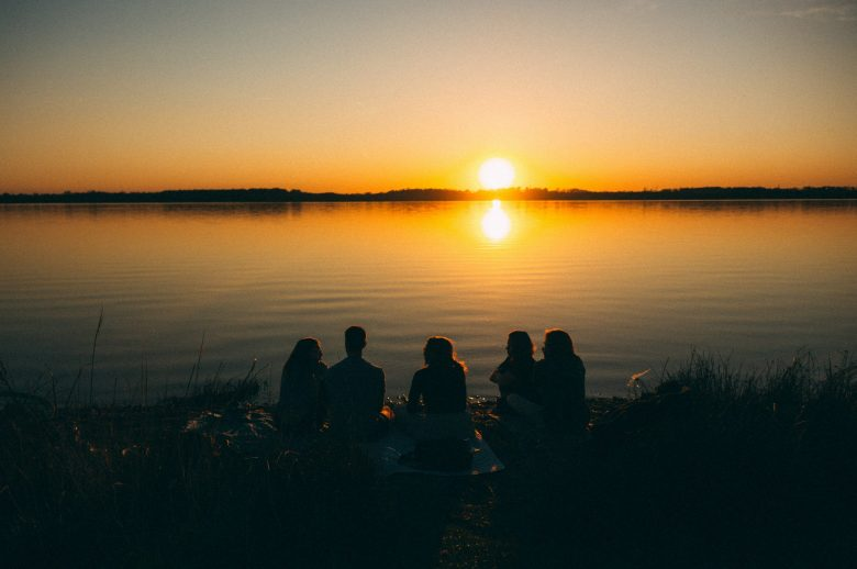 夕暮れの水辺に座って話す人達