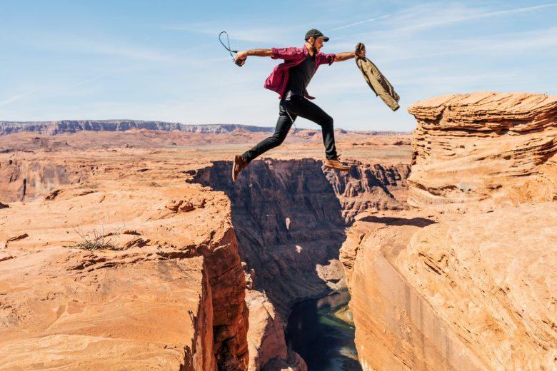 崖を飛び越える男性