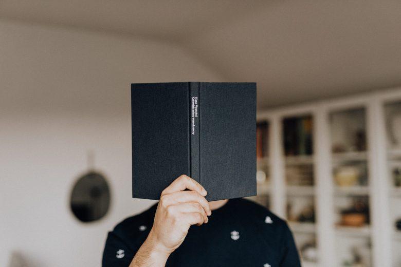 本を開いて顔を隠す人