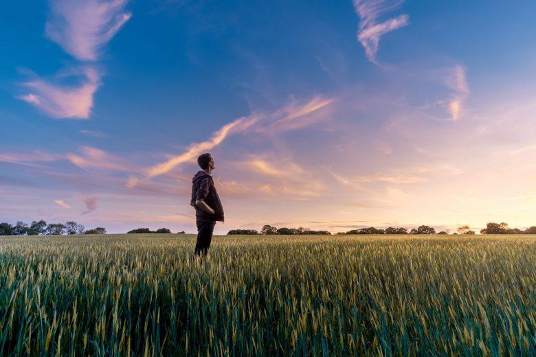 草原に立ち空を見上げる男性