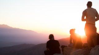 崖の上から夕陽を眺める3人組