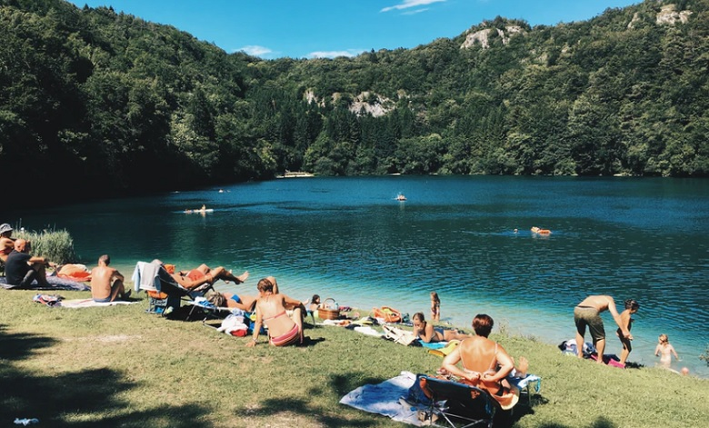天気の良い日に湖畔でくつろぐ人達