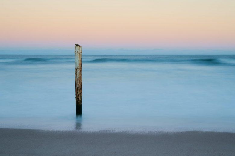 海岸に立つ白いポスト
