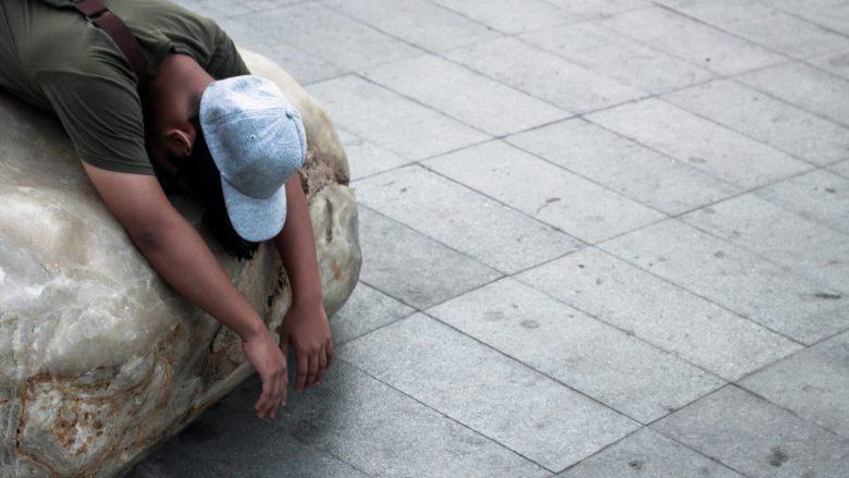岩の上で寝ている男性