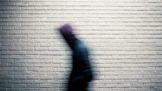 白い壁の前を急いで動く人