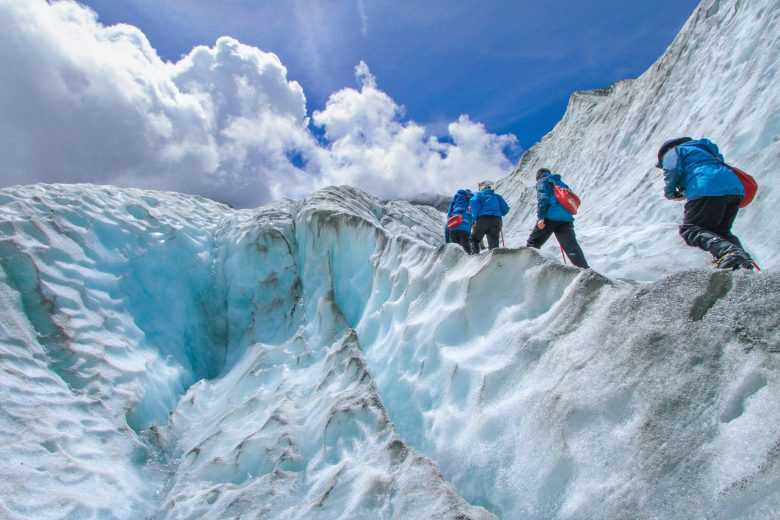昼間に雪山を登る4人組