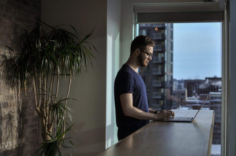 立ちながらノートパソコンを操作する男性
