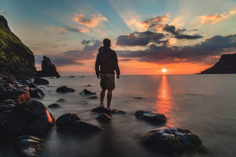 海辺の岩の上で夕日を眺める男性