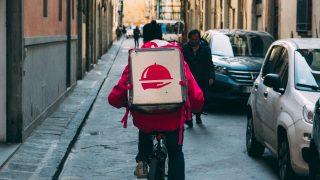 荷物を背負って自転車に乗る男性