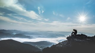 崖の上に座る男性