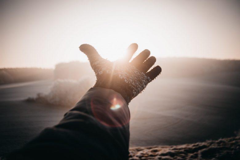 朝日に向かって手を伸ばす人