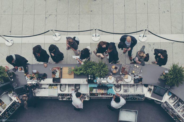 フードカウンターに並ぶ人達の空撮写真