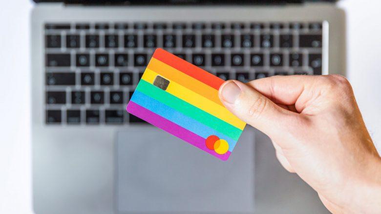 パソコンの前にクレジットカードをかざす人