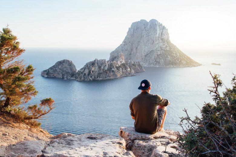 崖の上から海を眺める男性