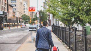 赤いバッグをひいて歩くスーツ姿の男性