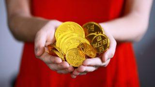 両手にコインを持つ赤いドレスを着た女性