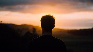 夕日を見ている男性のシルエット