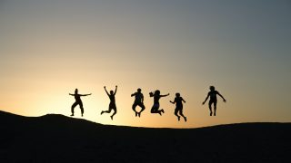 日の出を背景にジャンプする人達の影