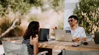 屋外でパソコンを操作しながら談笑する男女