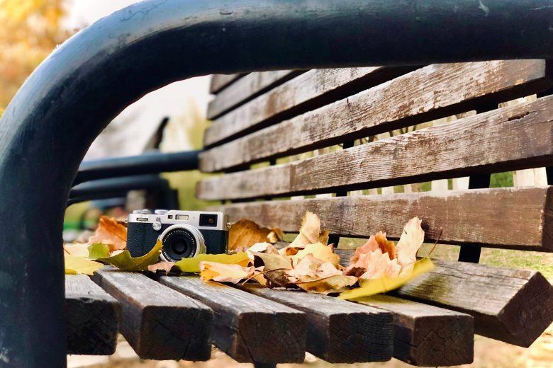 ベンチの上にあるカメラと落ち葉