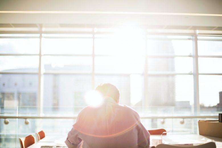 日が差す場所に座っている男性