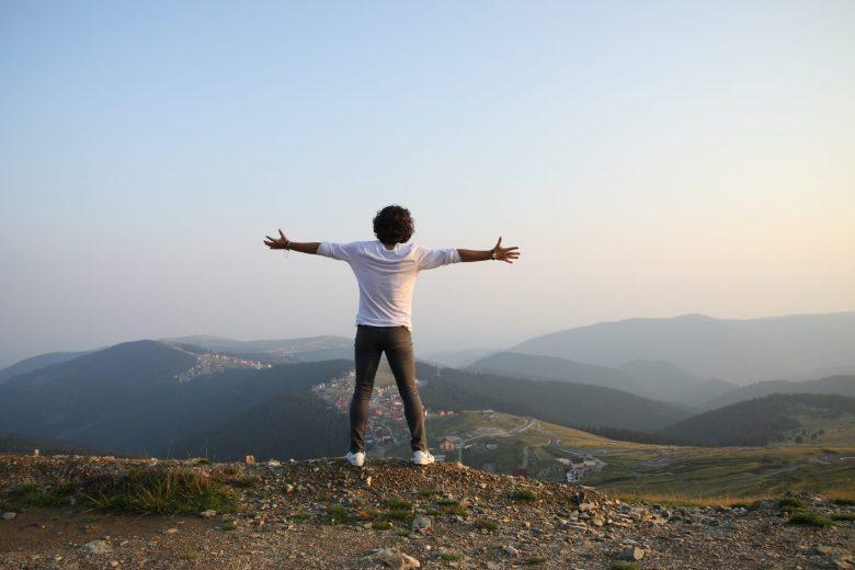 崖に立って手を広げる人