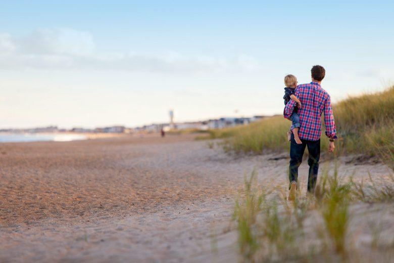 息子を抱いて海岸を散歩する父親