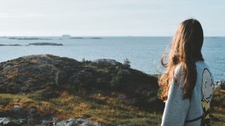 灰色のジャケットを着た女性が海を見つめる様子